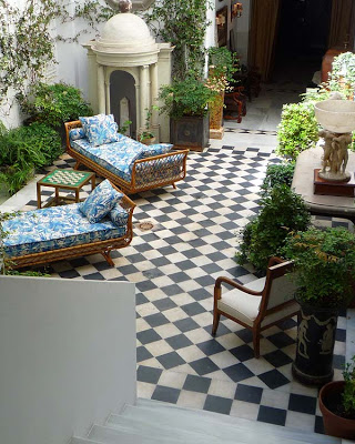 Checkered black and white floor in a couryard with rattan daybeds