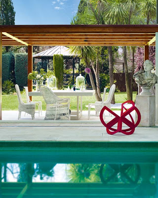 swimming poll with pergola in the back and modern red sculpture