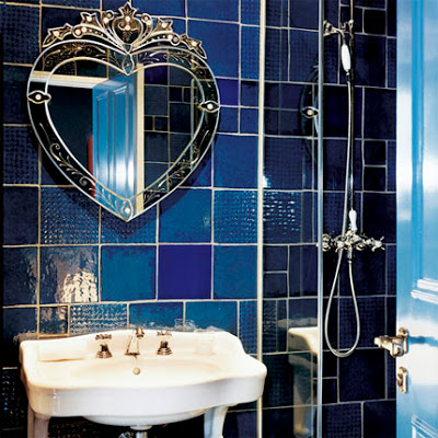 French style bathroom design blue tiles, white sink and venetian mirror
