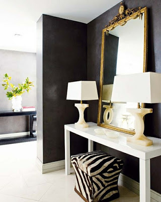 entry way in black walls and white table and zebra stool via belle vivir blog
