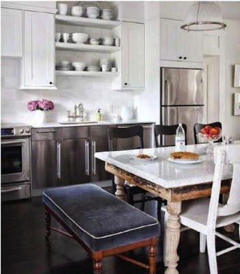 kitchen with dar floor, white cabiners, destressed table and floor to ceiling tiles