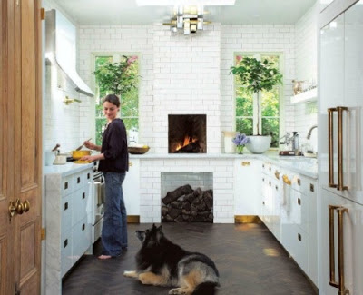 white kitchen with floor to ceiling tiles on the walls and fireplace via belle vivir