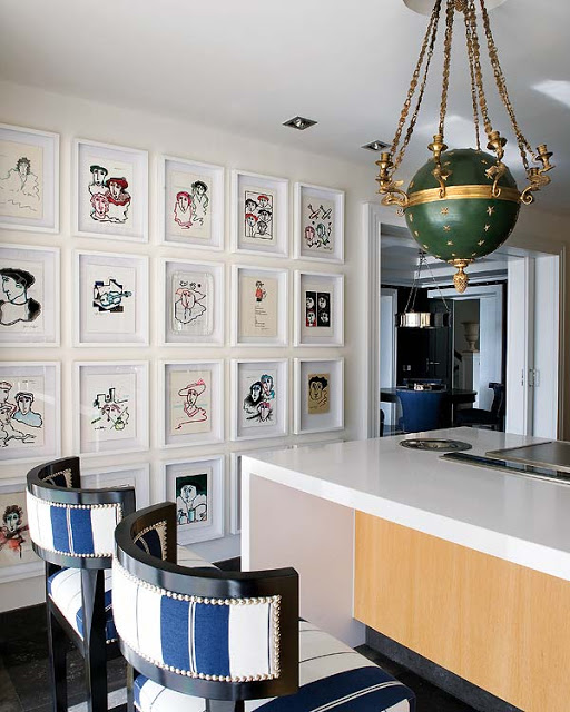 a gallery wall in a kitchen with colorful dowings framed in white frame