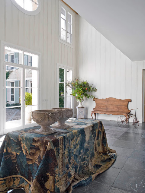 an entryway with a skirted table and ship lap walls