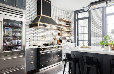 white kitchens with black stoves, swbuay tiles with grey grouts, blue cabinets and black LaChanche stove