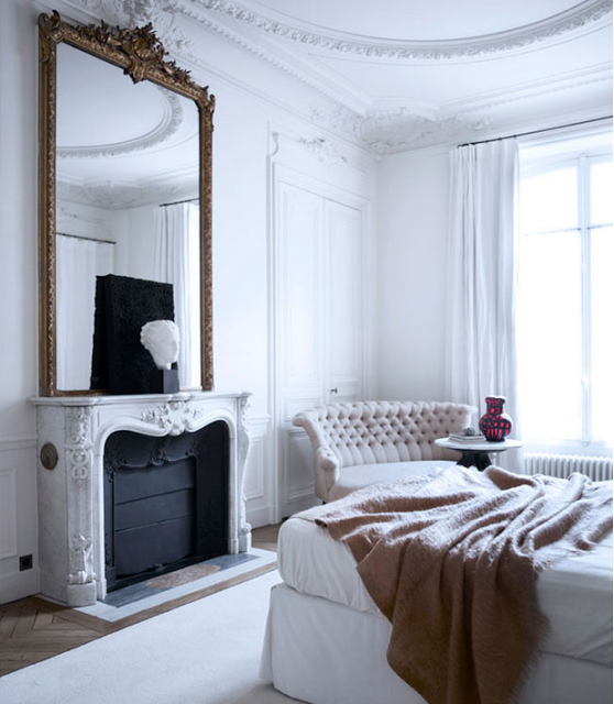 bedroom design by Gilles and Boissier with white fireplace and ornate walls