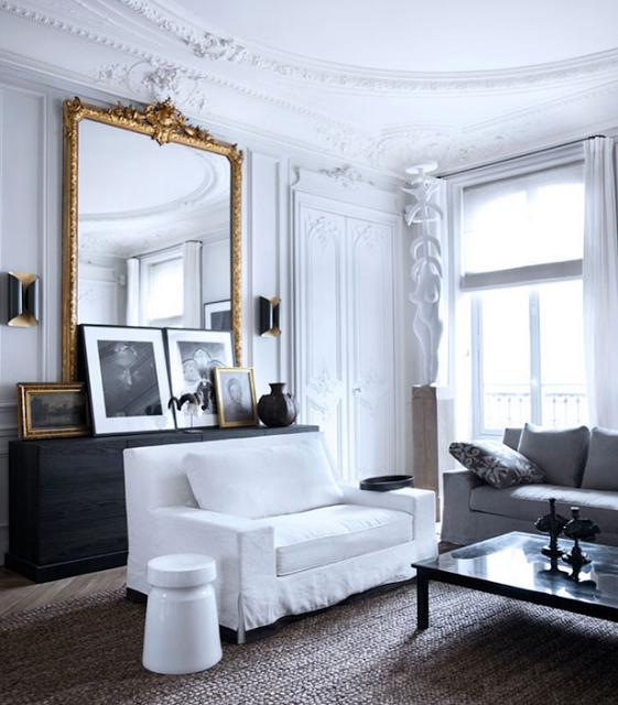 Gilles & Boissier design living room with golden mirror black and white art and jute rug and slipcovered sofas via belle vivir blog