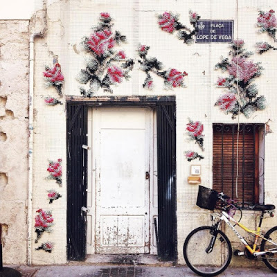 motivational quote image of a wall with flowers and a bike on cabblestone street