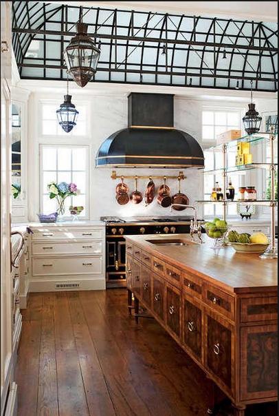 White cabinets, copper hanging pots, black la corneu range and wood island