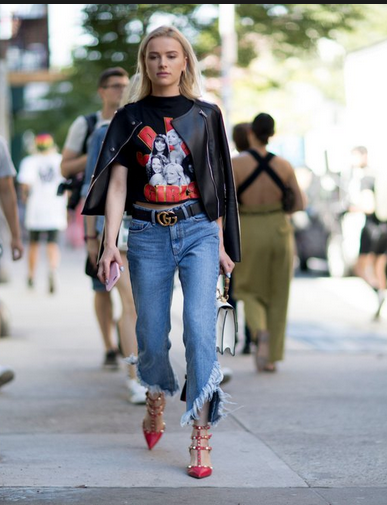 a girls wearing valentino studded shoes, ripped on the ankles jeans and black t-shirt