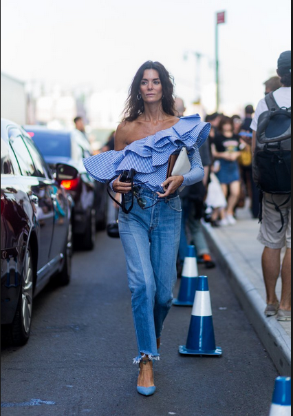 girl wearing ripped in the ankle jeans and one shoulder ruffle top