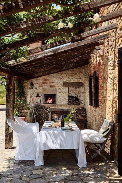 outdoor sitting with white slipcover under pergola with flowers and stone walls