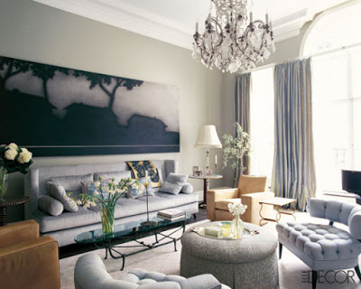 living room with different shades of blues and greys, crystal chandelier and leather chairs