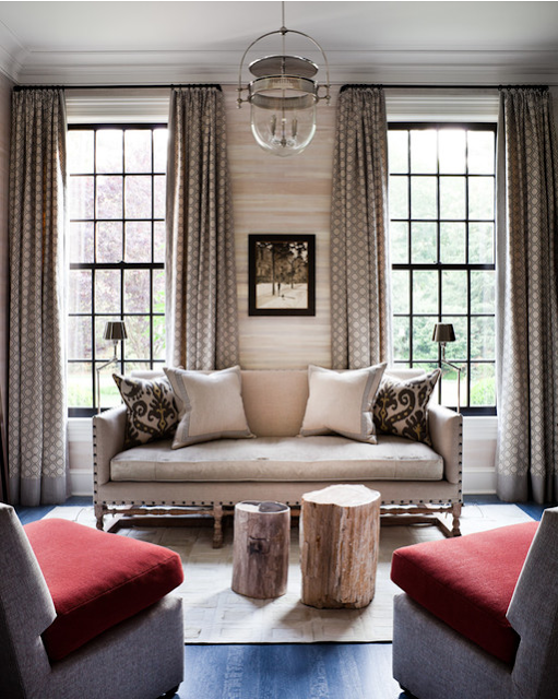 transitional interior design cozy seating area with uphlstered sitting and curtains. red pillows seat on side chairs