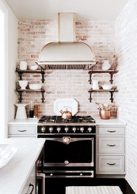 brick white washed wall, black stove, chrome hood and grey cabinets kitchens with black stoves