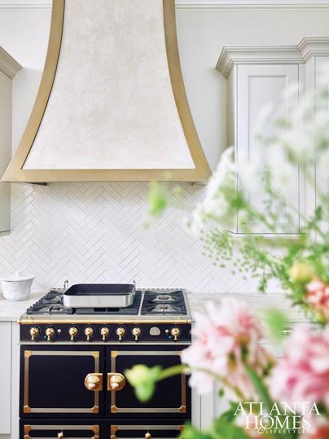 herringbone white tiles as backsplash, white cabinets and black with brass trim stove