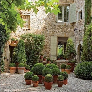 Provencal Gardens design ideas with terracotta pots with boxwood and stone walls and shutters