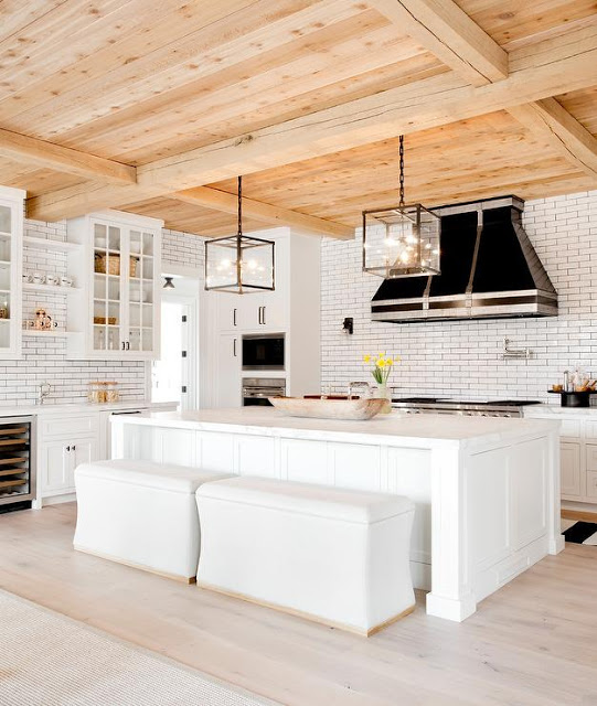 black and white kitchen design, beam ceiling, black stove and hood and glass upper cabinets